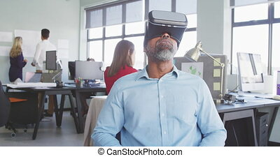 Front view of an African American male business creative working in a casual modern office, sitting and using a VR headset with colleagues in the background in slow motion