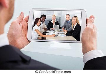 Businessman Video Conferencing On Digital Tablet At Desk