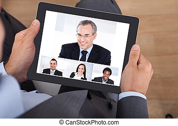 High angle view of businessman video conferencing with coworkers on digital tablet in office