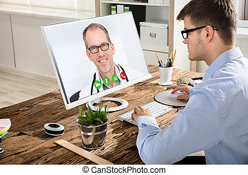 Businessman Video Conferencing With Doctor On Computer