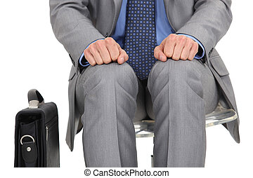 businessman waiting at station with briefcase by his side