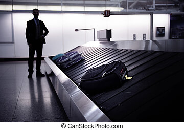 Businessman waiting for suitcase on luggage conveyor belt,...