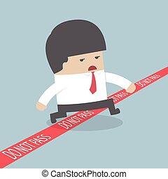 Businessman walking across a red li