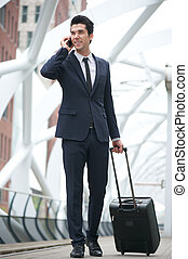 Businessman walking and talking on the phone at metro station