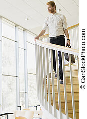 Businessman walking down the stairs whilst holding a bag