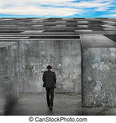 Businessman walking enter the huge maze with blue sky clouds