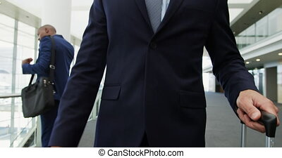 Front view close up of a young Caucasian businessman with a suitcase walking through the lobby of a modern office building with business people using smartphones in the background