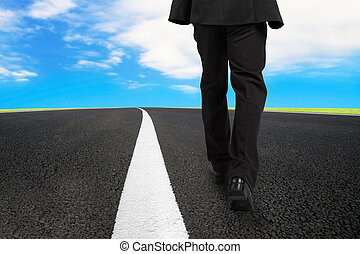 Businessman walking on asphalt road with sky clouds