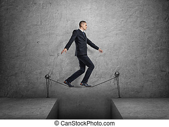 Businessman walking on drawn tightrope over the gap - A...