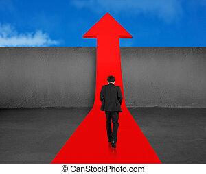 Businessman walking on growing red arrow