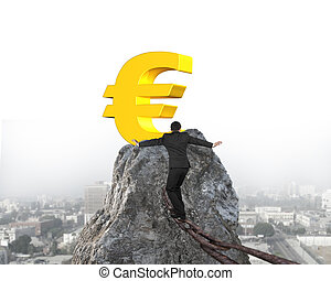 Businessman walking on iron chain toward euro symbol with cityscape