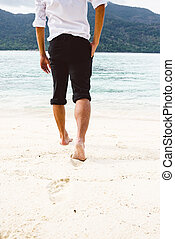 Businessman walking on sand beach with golden sand and sea wave, success, winner, leader concept