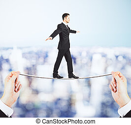 Businessman walking on the rope in the hands concept