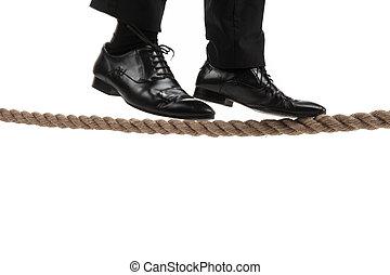 businessman walking on tightrope on white background. ...