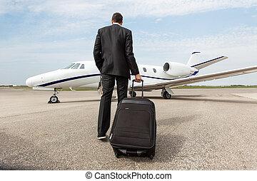 Businessman Walking Towards Corporate Jet - Rear view of...