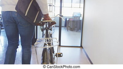 Side view mid section of an African American male business creative arriving at a casual modern office wheeling a bicycle, with colleagues working in the background
