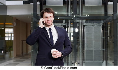 Businessman walking with coffee and briefcase on phone.