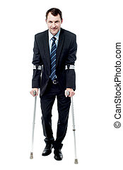 Businessman walking with crutches