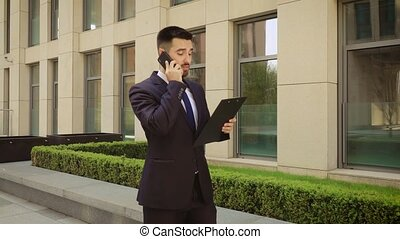 Businessman walks down the street with a tablet and talking...