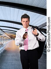 Businessman walks on a modern corridor and he is playing or dialing on his mobile phone.