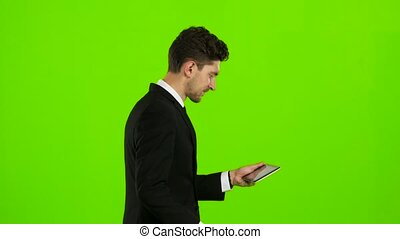 Businessman walks, thumbs a notebook, and makes a selfie....