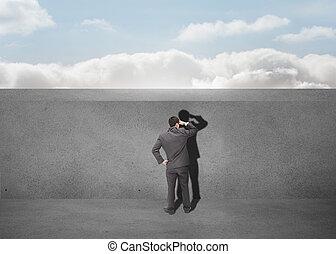Businessman watching a grey wall
