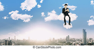 businessman watching smart phone and sitting on the cloud