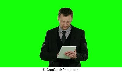 Businessman watching something in laptop and smiling. Green screen