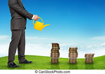 Businessman watering coins