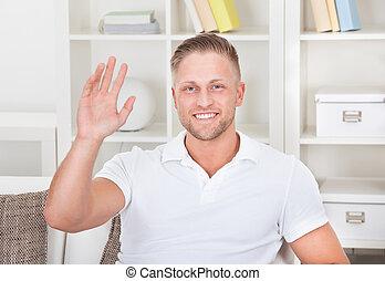 Businessman waving in pleasure to his laptop