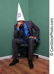 Businessman wearing a dunce hat