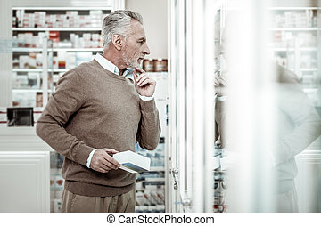 Businessman wearing brown trousers standing near glass windows in pharmacy