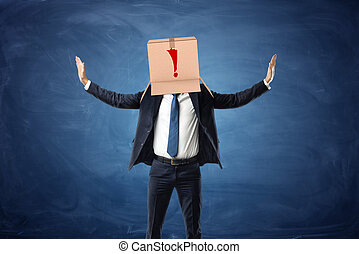Businessman wearing cardboard box with drawn exclamation point on his head.