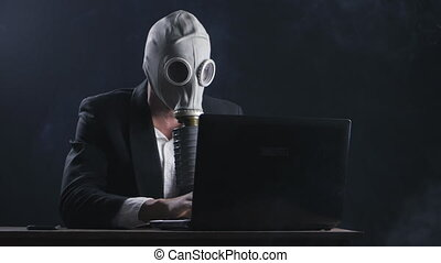 Businessman wearing gas mask working at laptop in dark office