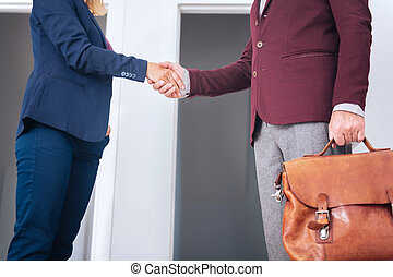 Businessman wearing grey trousers shaking hand of his future female partner