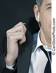 Businessman Wearing Headphones Straightens Jacket