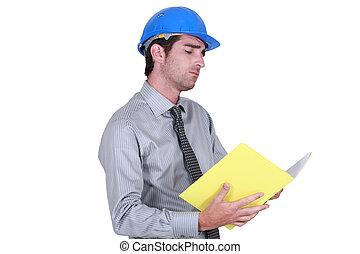 businessman wearing helmet taking notes