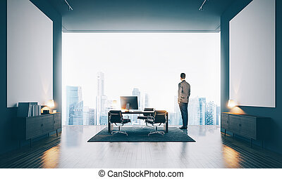 Businessman wearing modern suit and looking at the city in contemporary office. Horizontal