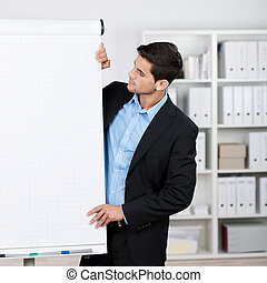 Businessman wearing suit looking at flipchart