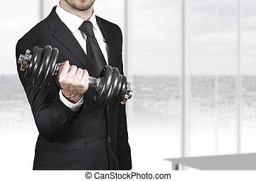 businessman weightlifting in office - businessman in black...