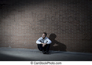 businessman who lost job lost in depression sitting on city...