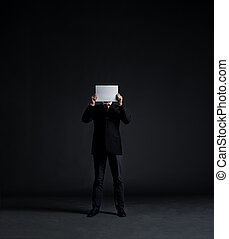 Businessman with a blank paper over his face. Black background with copy space. Business and office concept.