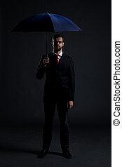 Businessman with a blue umbrella in a studio