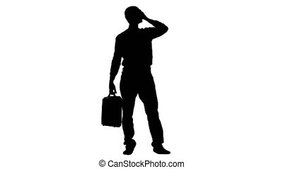 Businessman with a briefcase in his hands is thinking about business. Silhouette White background