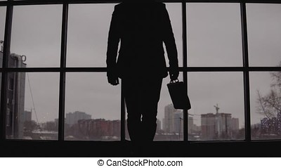 businessman with a case in hand goes to the window in the office and looks at the city
