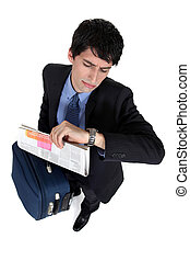 Businessman with a case looking at his watch