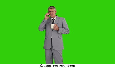 Businessman with a cup of tea having a phone call