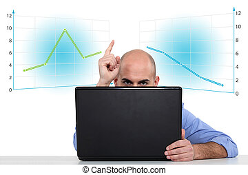 Businessman with a laptop and graphs