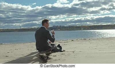 Businessman with a laptop suitcase working relaxing on the beach