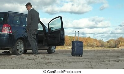 Businessman with a laptop suitcase working relaxing on the beach near his car.